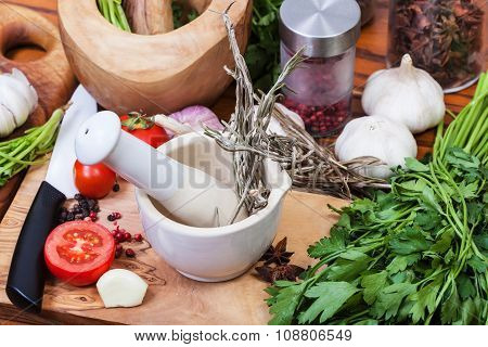 Pestle Herbs In Ceramic Mortar And Spices On Table