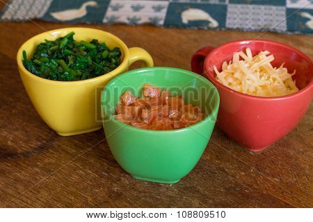 Ingredients in colorful cups on wood table