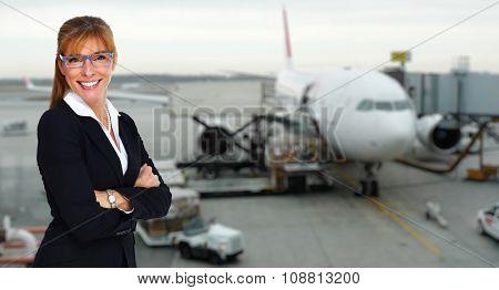 Beautiful smiling stewardess woman near airplane. Travel concept.