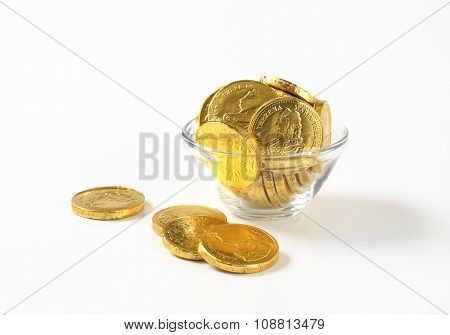 bowl of chocolate coins on white background