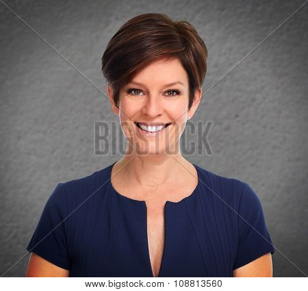 Beautiful mature business woman over gray wall background.