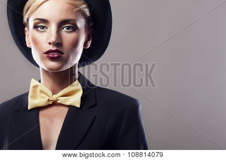 Woman In Hat And Yellow Bow On Grey Background