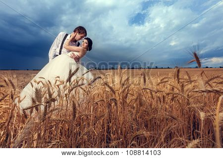 Bride And Groom In Wheat Field With Dramatic Sky