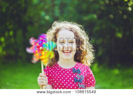 Little Girl With Rainbow Pinwheel Toy In Summer Park. Eco, Travel, Vacation, Family Concept.