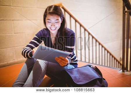 Smiling student sitting in hallway using laptop at the university
