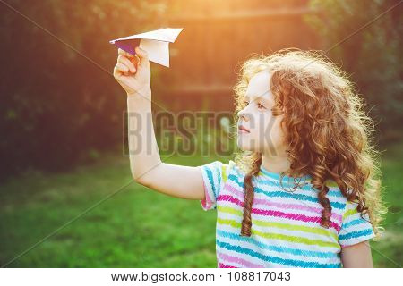 Cute Girl Throwing Paper Airplane At Summer Park. Happy Childhood, Travel, Vacation Concept.