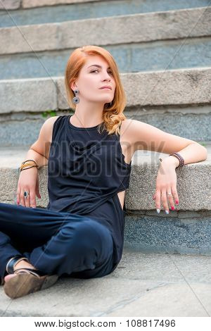 Pretty Girl Sitting On Concrete Stairs