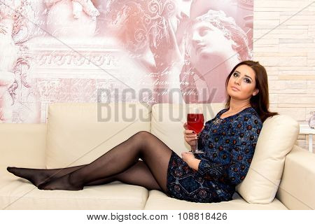 Beautiful Middle-aged Woman Sitting On The Couch With Glass Of Wine.