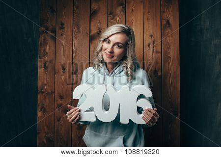 happy blonde woman holding 2016 numbers