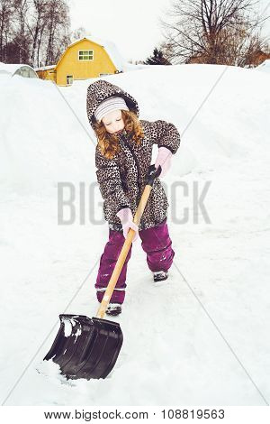Child Is Shoveling Snow In Front Of His House.