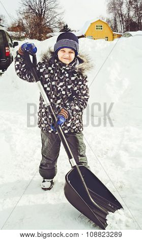 Child is shoveling snow in front of his house. Cleaning of snow after a snowfall.