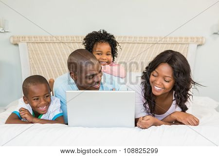 Family having fun together in bed with laptop