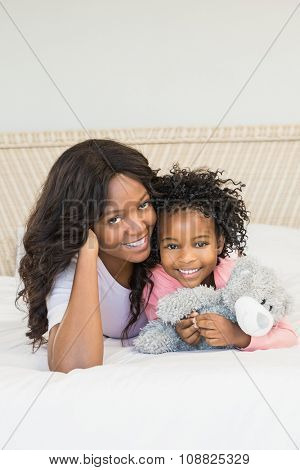 Mother and daughter smiling on bed
