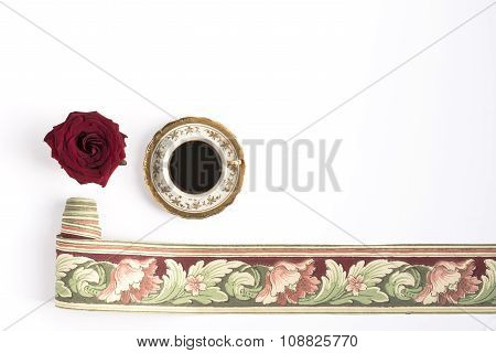 Cup of coffee with red rose and roll of wallpaper