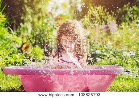 Happy curly girl taking water procedures in summer garden.