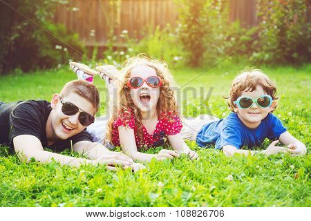 Happy Children In Glasses Lying On The Grass. Happy Family Concept.