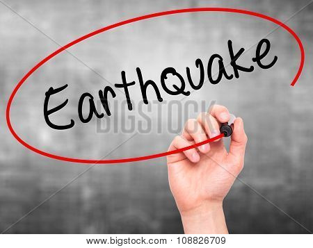 Man Hand writing Earthquake with black marker on visual screen.