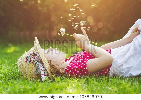 The Child Lays On A Grass And Blowing Dandelion In The Rays Of The Sun. Background Toning For Instag