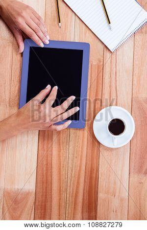 Overhead of feminine hands using tablet with black espresso and notebook on desk