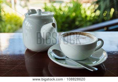 Cup Of Coffee With Hot Tea Pot On Wooden And Blur Background