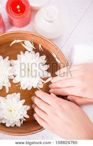 Pleasant woman holding flower on the spa bowl