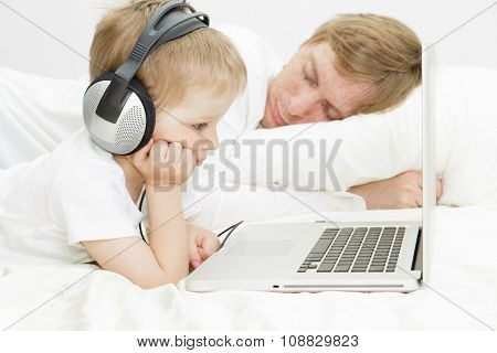 child in headsets with computer while father is asleep