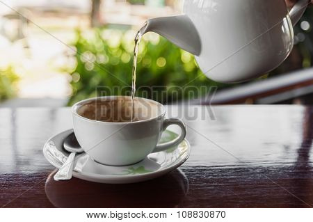 Cup Of Coffee With Water Splashing From Hot Pot On Wooden, Still Life Tone