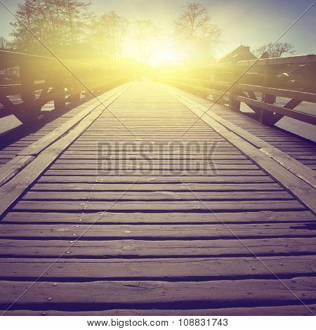 Wooden bridge over river at sunset. Vintage style.
