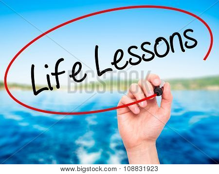 Man Hand writing Life Lessons with black marker on visual screen.
