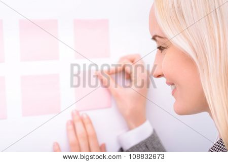Pleasant businesswoman working with stickers