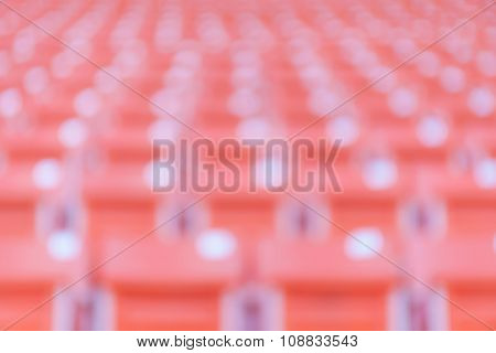 Abstract Blurred Background Of Empty Red Stadium Chairs In A Row.