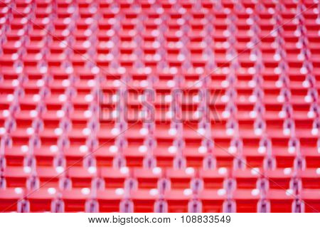Abstract Blurred Background Of Red Seats At Football Stadium.