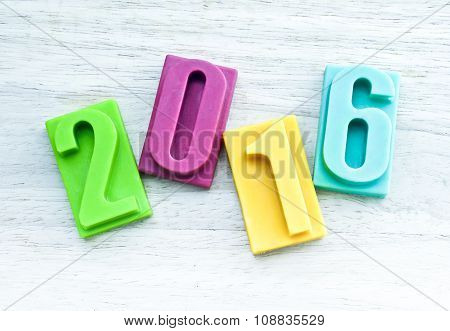 Happy new year 2016, bar of chocolate number on wooden background