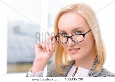 Nice businesswoman holding her glasses