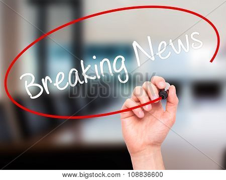 Man Hand writing Breaking News with black marker on visual screen.