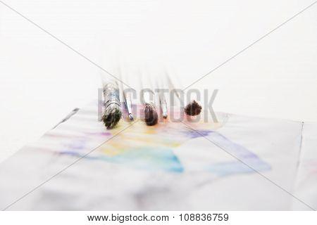 paint brushes lying on painted background