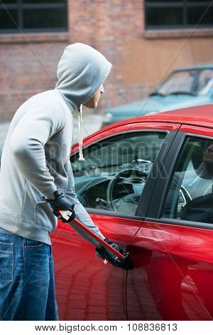 Thief Using Crowbar To Open Car's Door