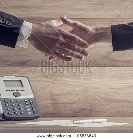 Business Partners Shaking Hands Over A Signed