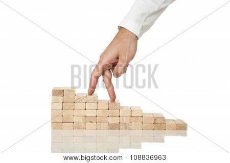 Male Hand Walking His Fingers Up Wooden Staircase Made Of Pegs