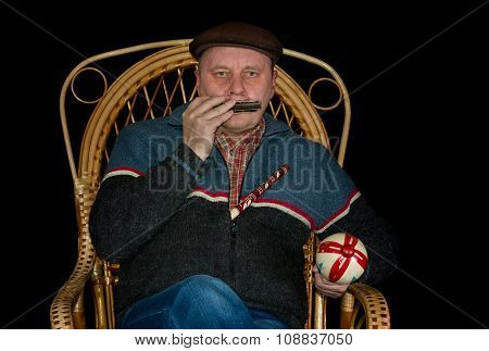 Portrait of mature man sitting in wicker chair