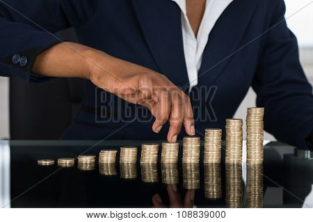 Person's Finger Walking On Pile Of Coins