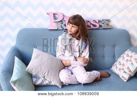 Girl  On The Sofa In Pajamas With Pillows