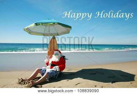 Santa Claus Poses with his Surf Board while on a Beach with the turquoise blue ocean and waves in the background. Santa Claus loves the beach. Focus on Santa's Face.