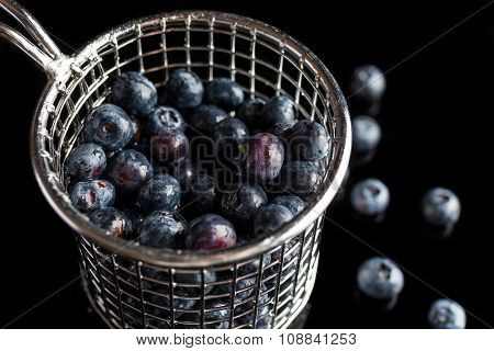 Blueberries in cup strainer from side high angle