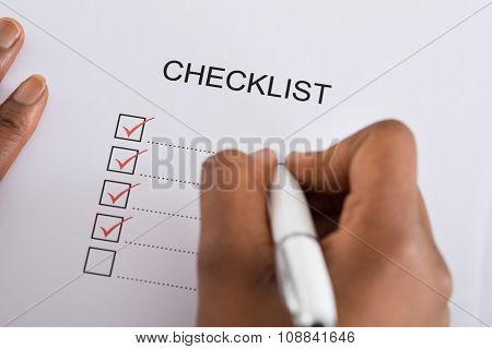 Person's Hand Marking Check Box With Red Pen