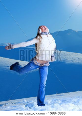 Happy joyful woman having fun in winter mountains in bright sunny day, playing on the snow, raised hands and leg, enjoying active wintertime vacation