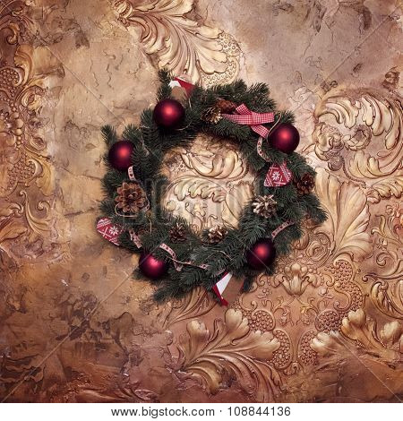 Christmas wreath on a golden wall,   fir branches with red balls and ribbons