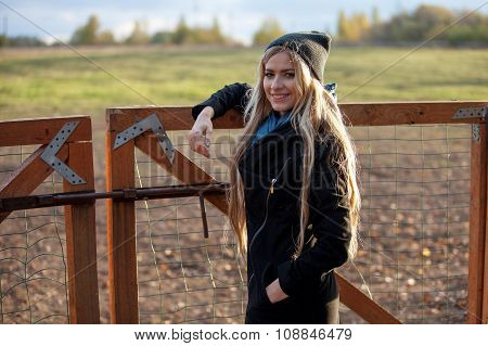 young beautiful girl in a stable, outdoors, woman at the fence