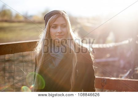 young beautiful girl in a stable, outdoors,  photo with warm toning, rays of sun