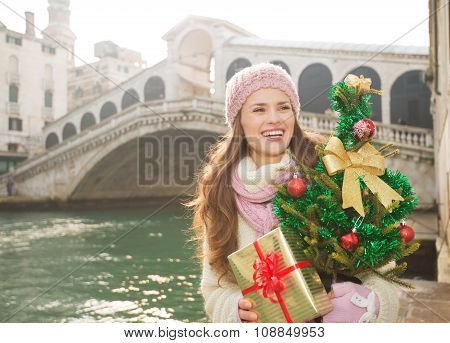 Smiling Woman With Christmas Tree And Gift Box In Venice, Italy